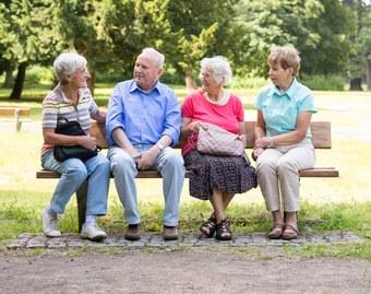 Ältere Menschen sitzen auf einer Bank im einem Park.