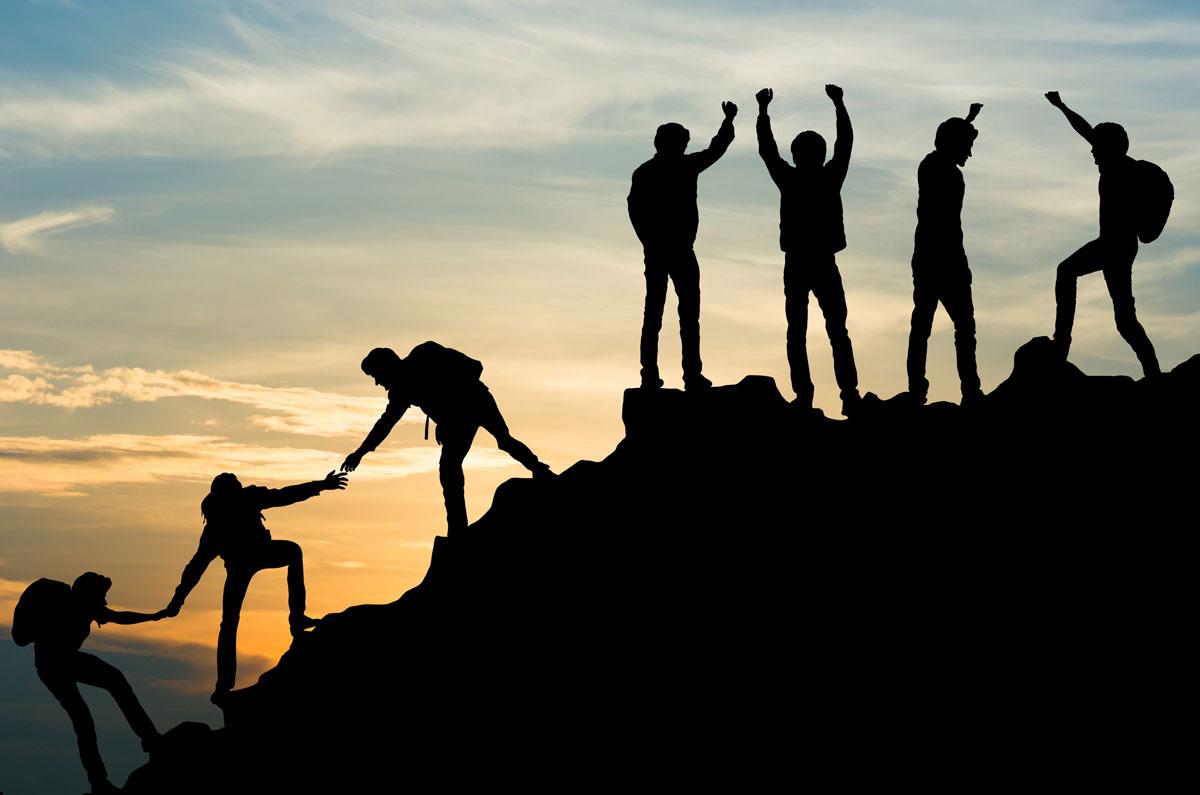 Fotografie: Fünf Bergstieger erklimmen bei Sonnenaufgang den Gipfel eines Berges.