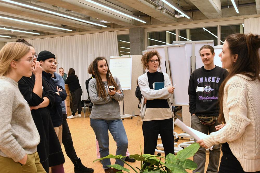 Studierende in der Freiform diskutieren an einem Marktplatzstand miteinander