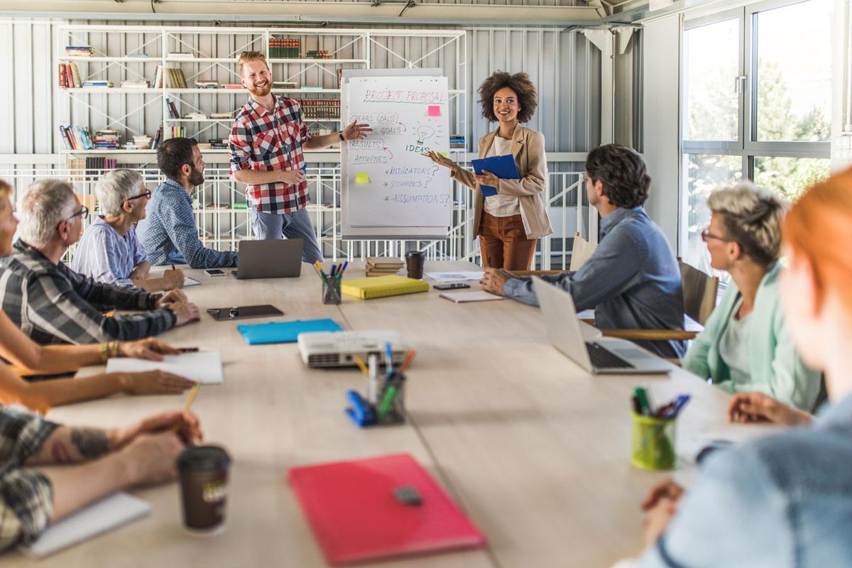 Ein Team sitzt in einem Büro um einen grossen ovalen Tisch und zwei Leute präsentieren etwas auf einem Flipchart.