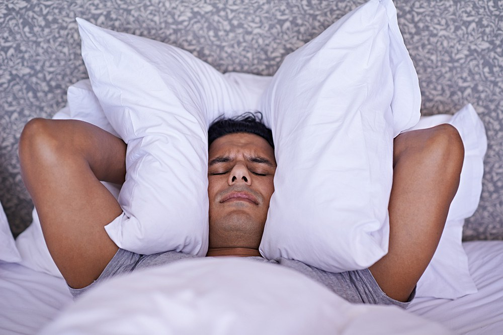 Ein Mann liegt im Bett und kann nicht schlafen. (©Getty Images/Yuri Arcurs)