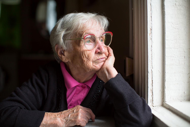 Eine Alte Frau sitzt an einem Fenster und schaut nachdenklich hinaus.