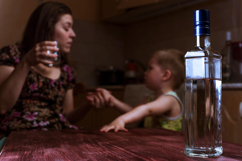 Mutter mit Kleinkind sitzen am Tisch. Die Mutter ha ein Glas mit Alkohol in der Hand.