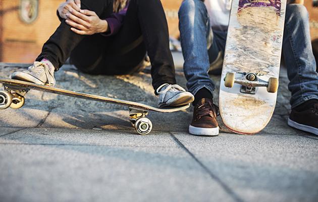 Zwei Jugendliche sitzen mit ihren Skateboards am Strassenrand