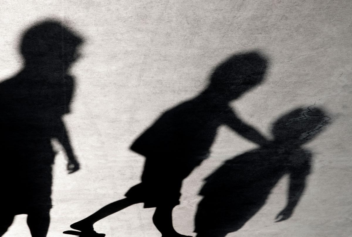 schwarze Schatten von drei Kindern auf weissem Hintergrund