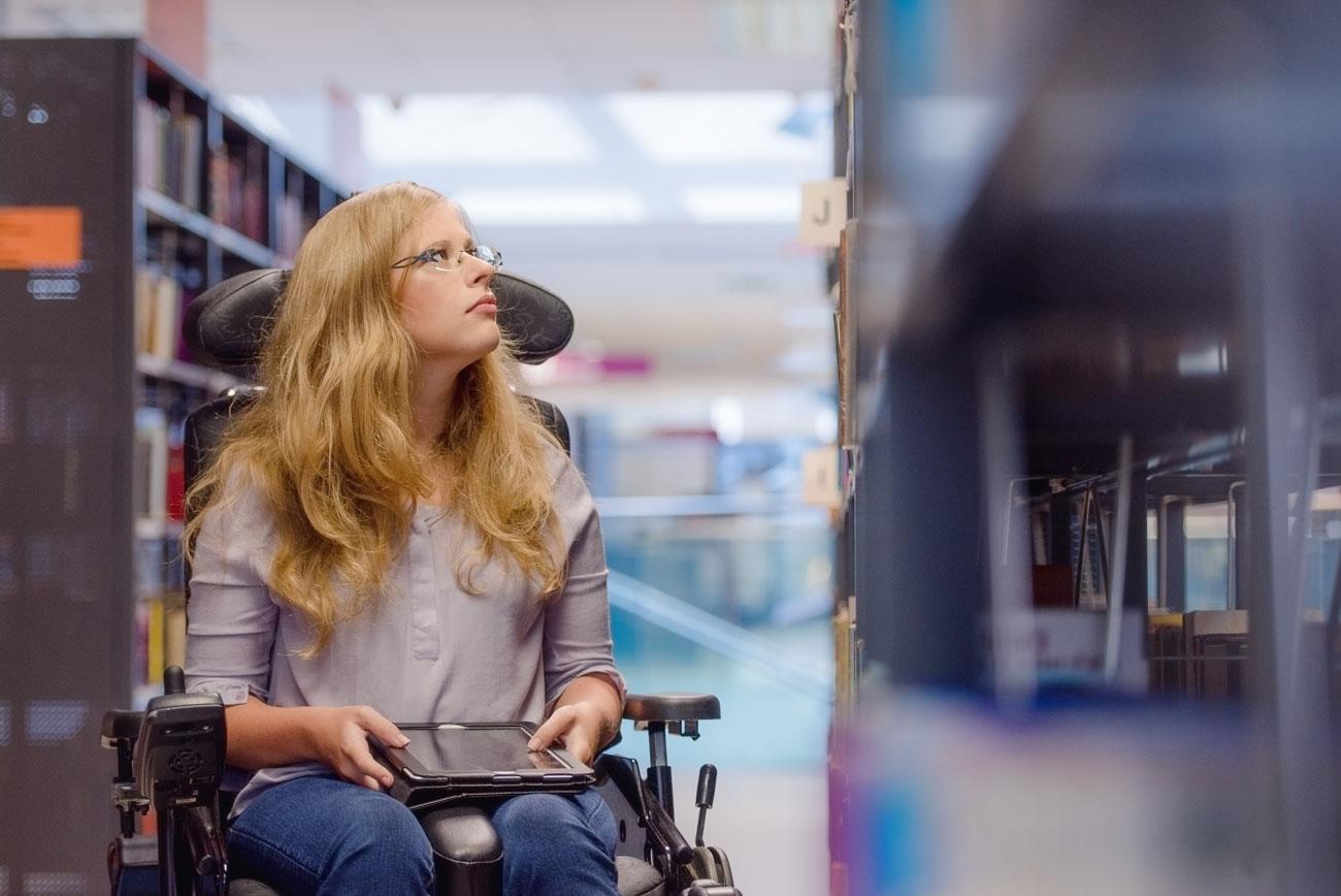 Eine Frau, die im Rollstuhl sitzt, hält ein Tablet in den Händen und befindet sich in einer Bibliothek.