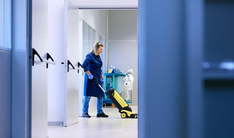 Eine Putzfrau putzt mit einem Staubsauger ein Büro.