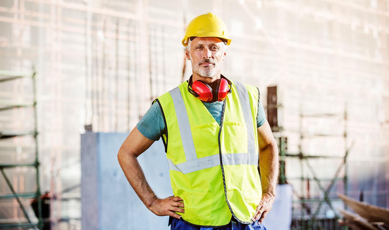 Ein Bauarbeiter steht vor einer Baustelle und schaut selbstbewusst in die Kamera.