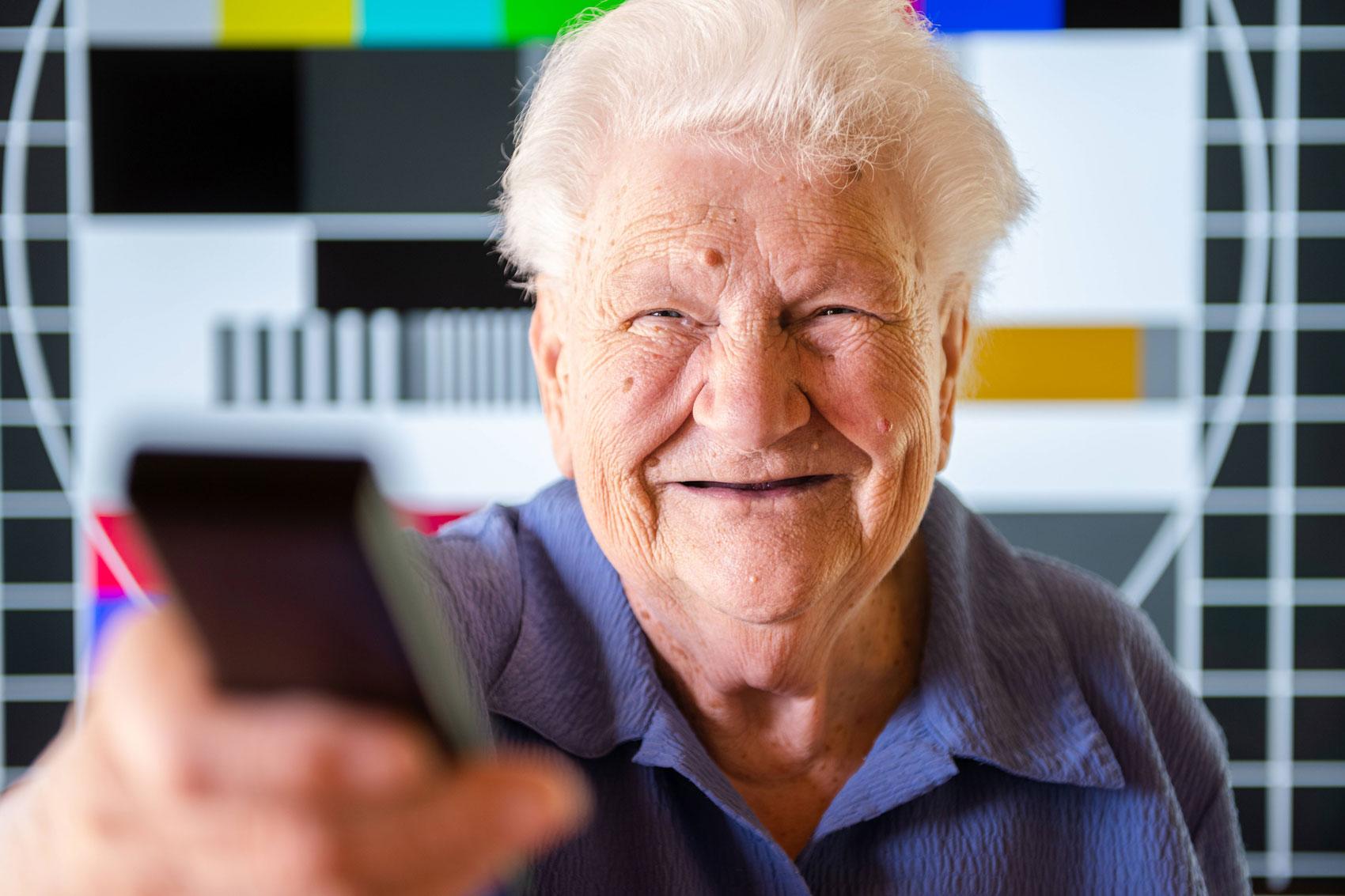Ältere Frau hält lächelnd eine Fernbedienung in Richtung der Kamera