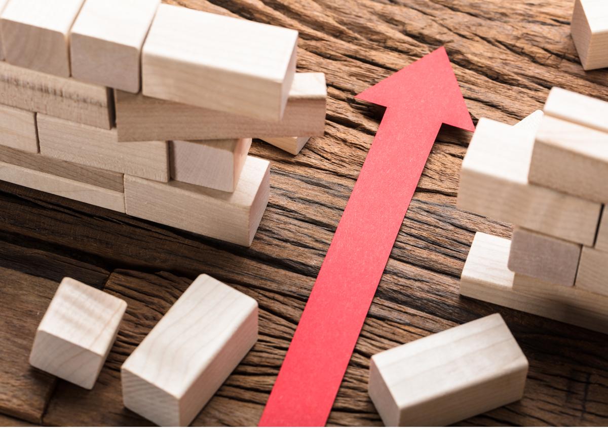 ein roter Pfeil durchbricht eine Mauer aus Holzklötzen