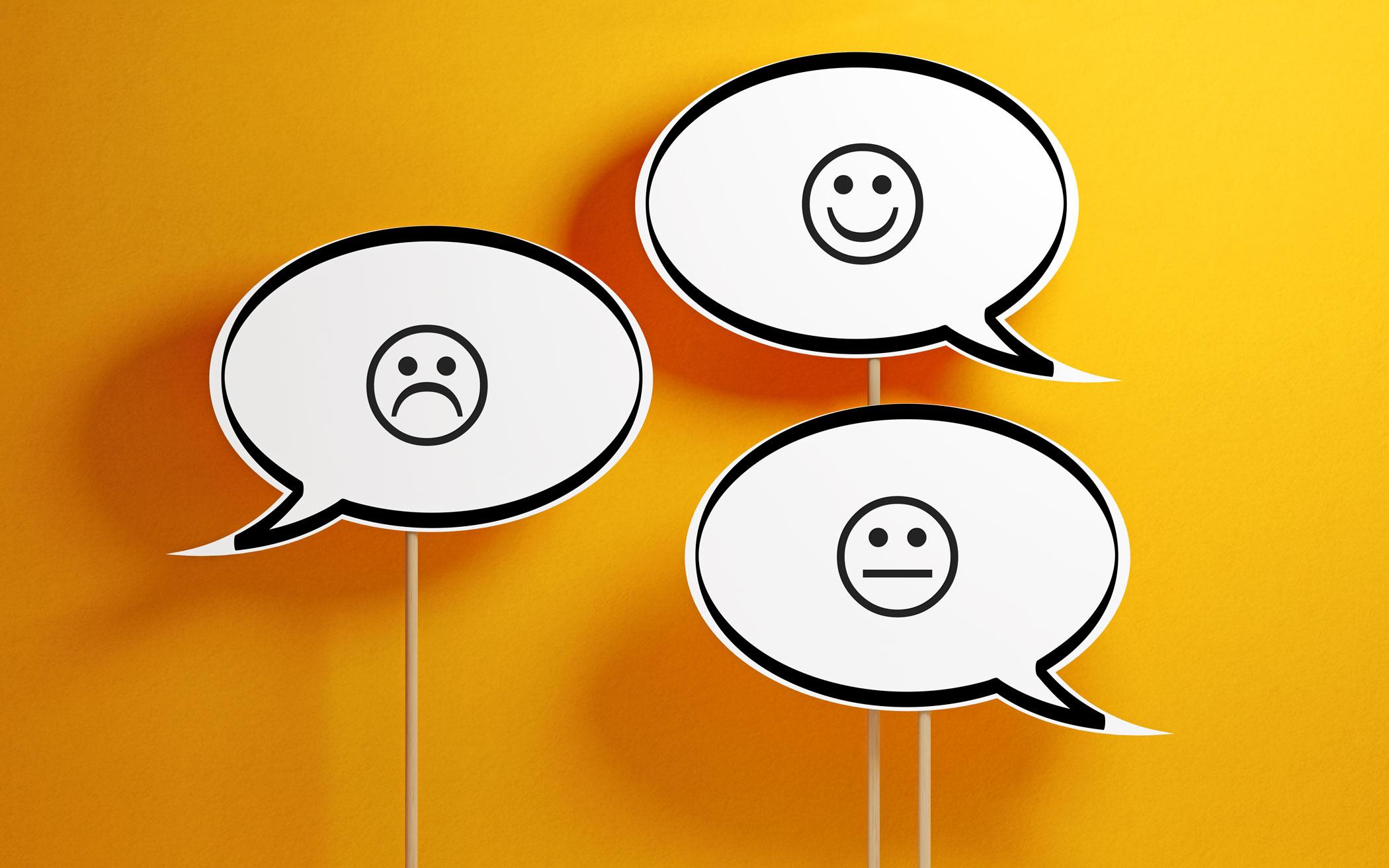 Drei Sprechblasen mit einem traurigen, fröhlichen und gleichgültigen Smiley.