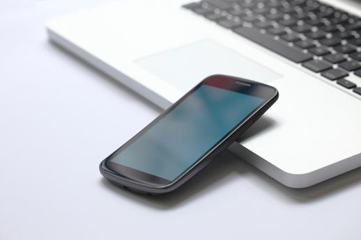 Ein Mobiltelefon liegt auf einem Laptop.