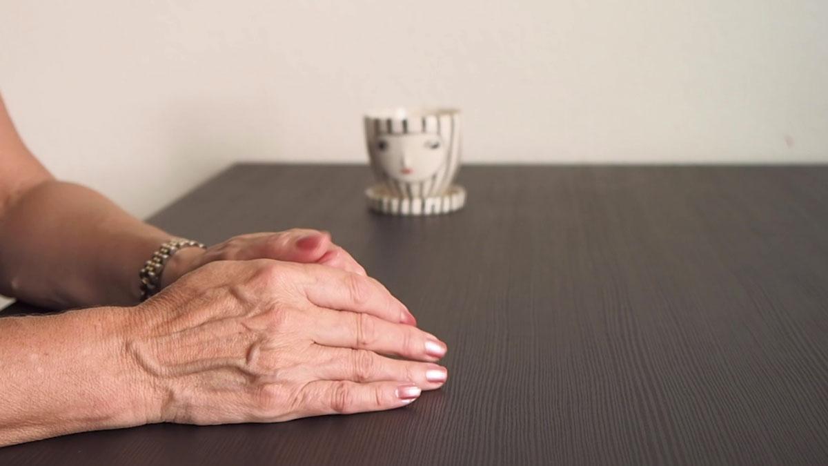 Hände einer interviewten Person liegen zusammengefaltet auf dem Tisch