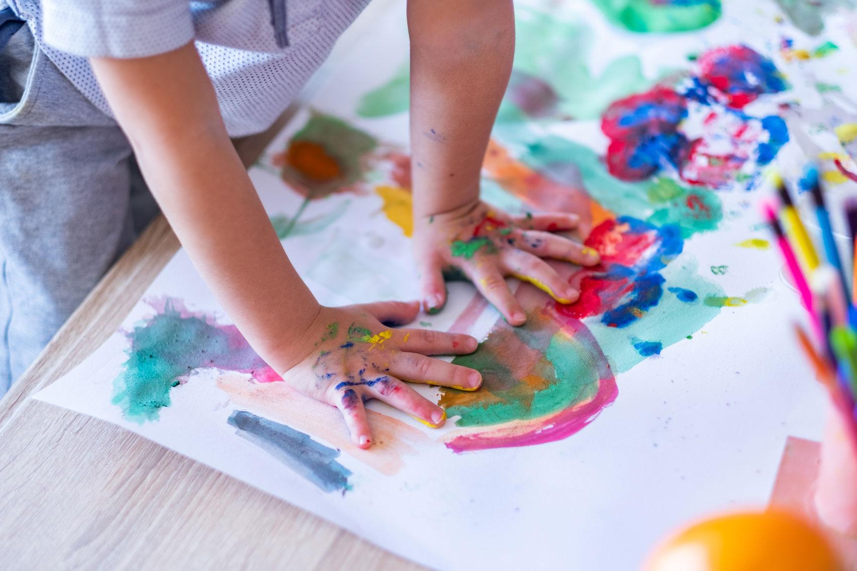 Ein Kind malt mit seinen Händen auf deinem Blatt Papier