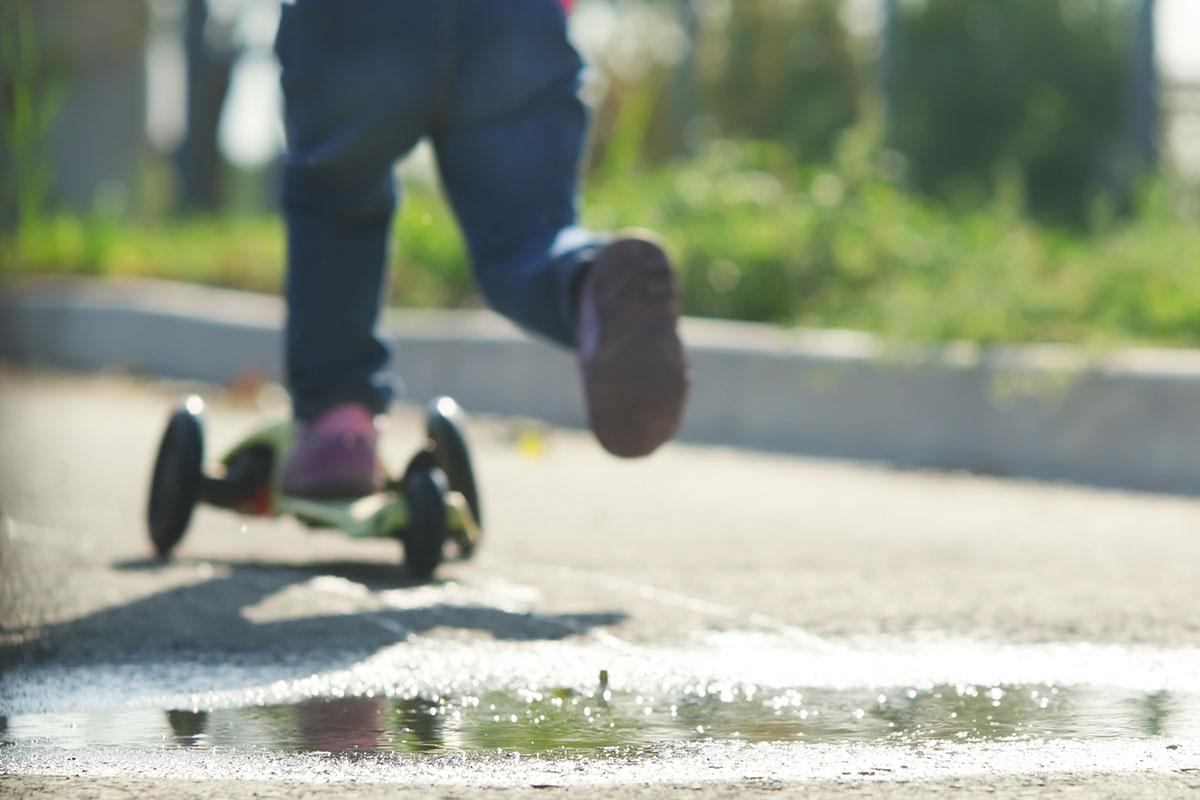 Kind fährt mit Trottinett auf der Strasse.