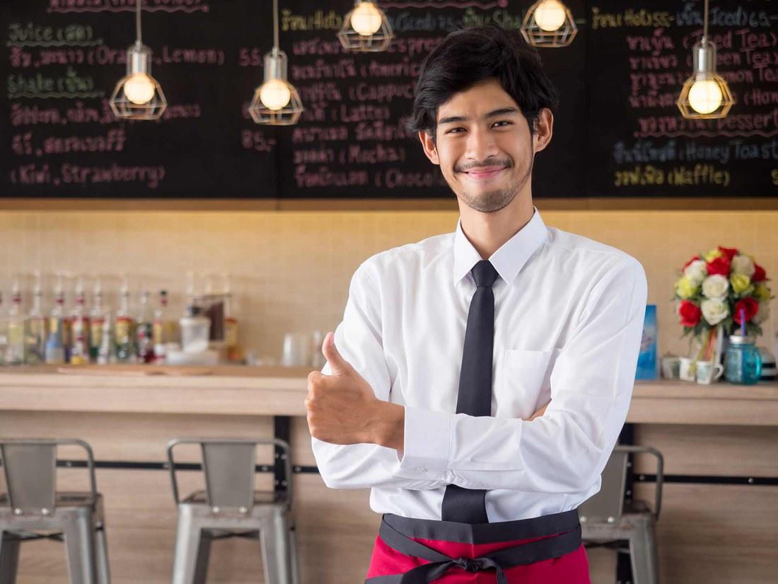 Ein junger Mann arbeitet in einem Gastronomiebetrieb. (©istock.com/Nattakorn Maneerat)