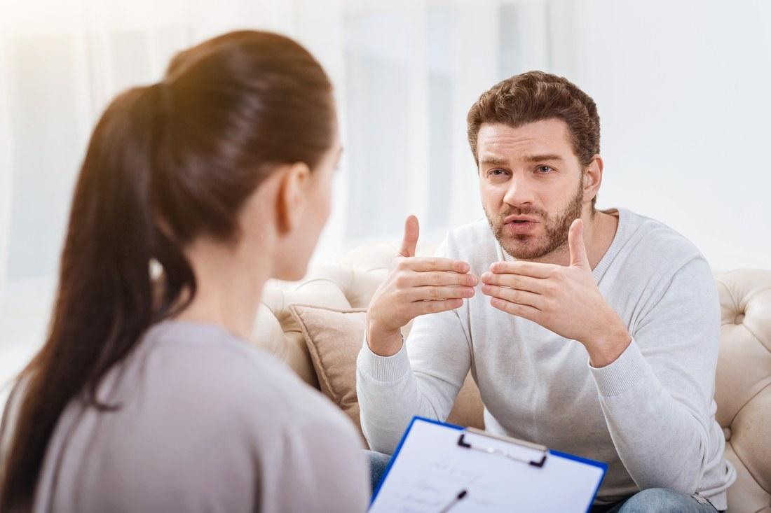 Eine Frau führt ein biografisches Interview mit einem Mann.