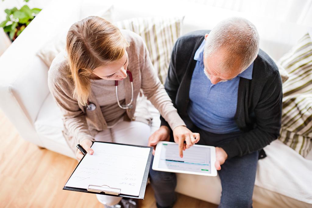 Eine Pflegefachfrau hilft einem älteren Herrn bei der Bedienung eines Tablets. (© Getty Images/Halfpoint)