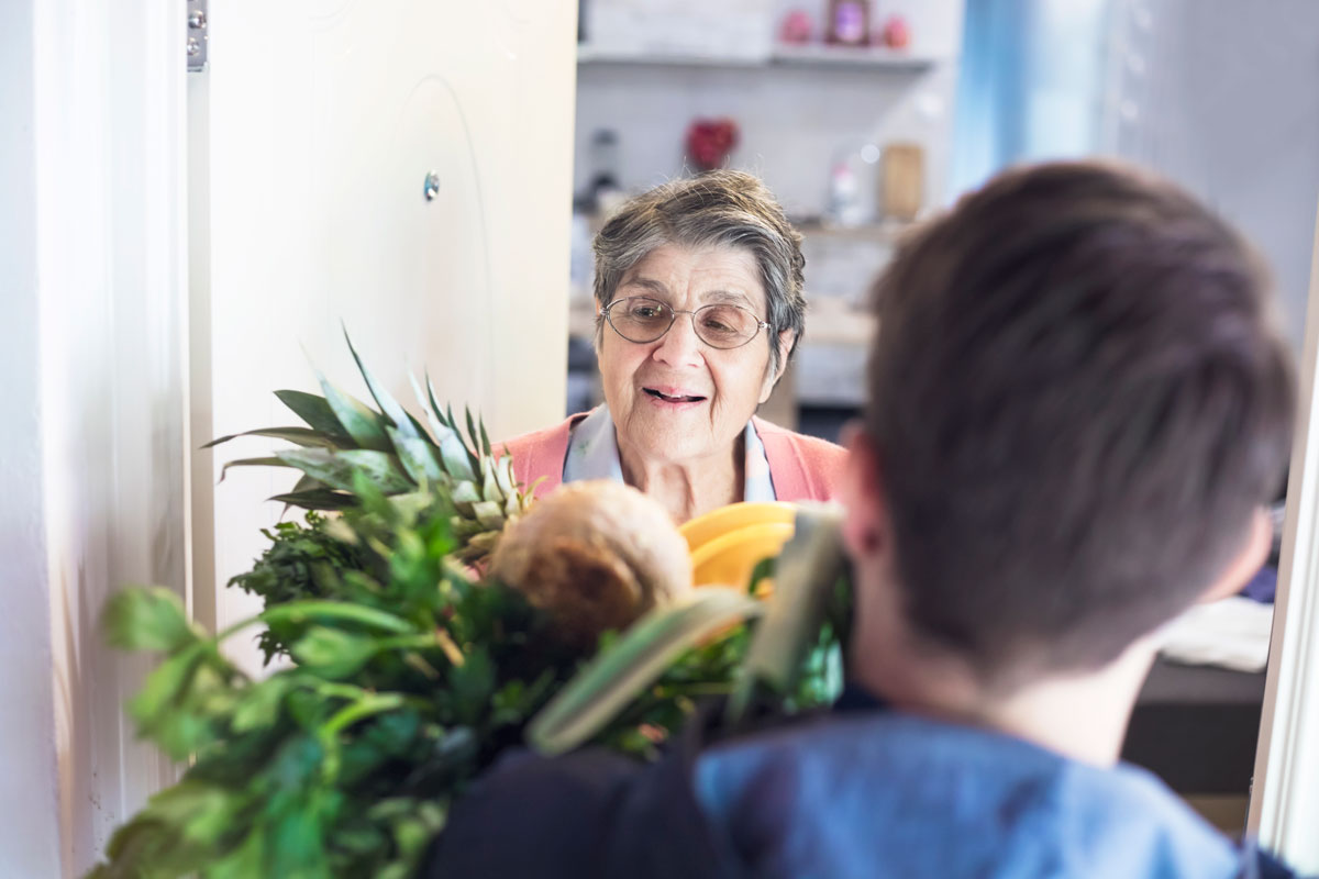 Fotografie: Mann bringt älterer Frau Essen nach Hause.
