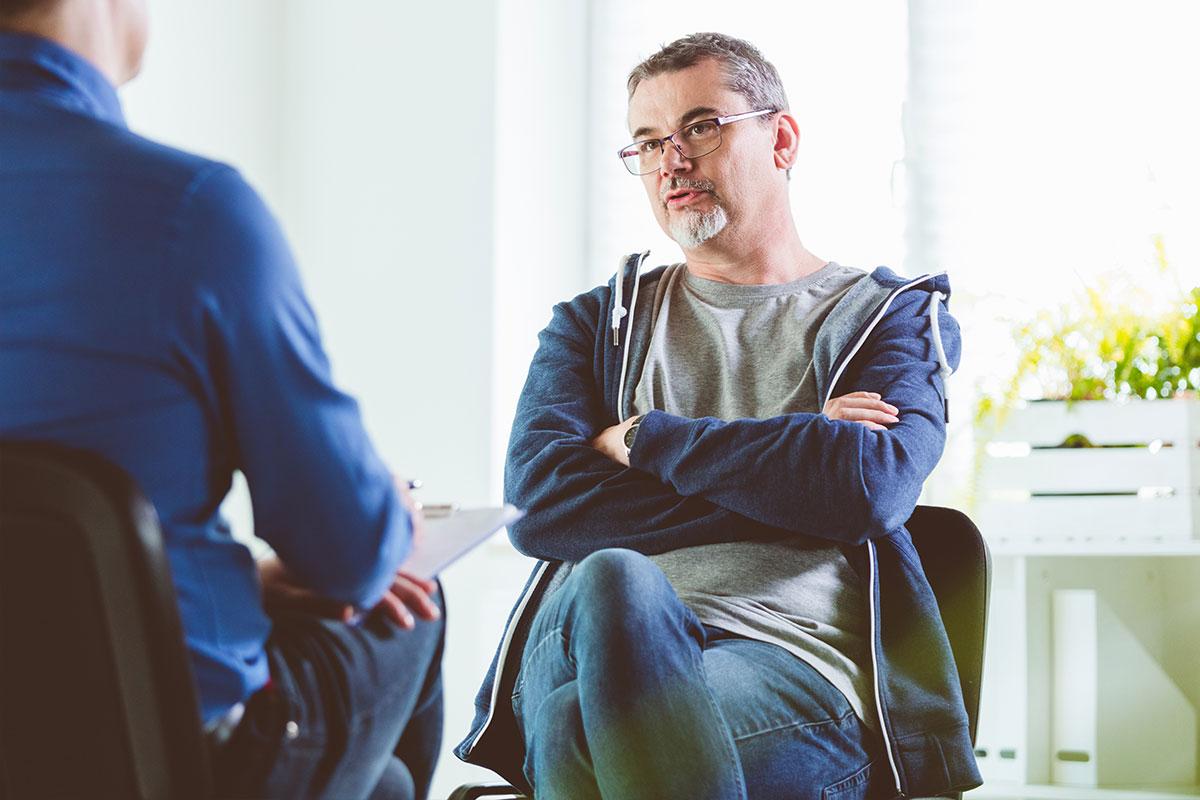 Zwei Männer sitzen gegenüber voneinander, einer ist Berater, der andere Klient.