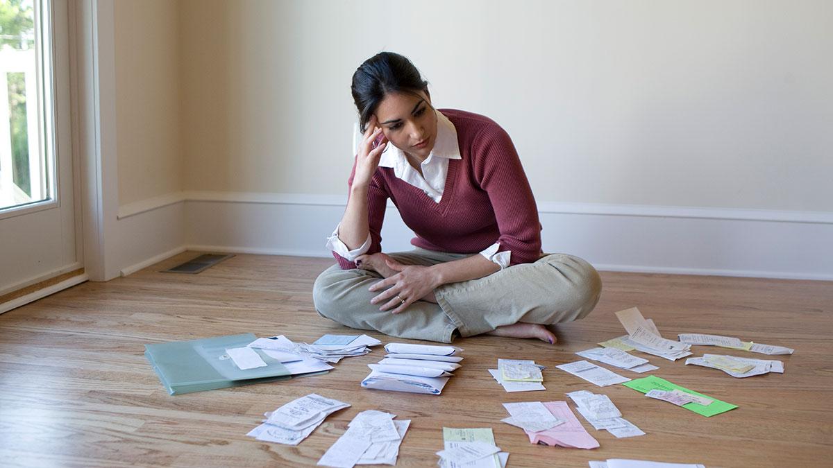 Frau sitzt am Boden mit vielen unbezahlten Rechnungen vor sich ausgelegt.