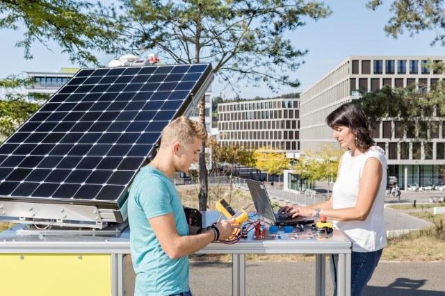 Zwei Lernende mit elektronischen Messgeräten neben einer Fotovolatiktafel