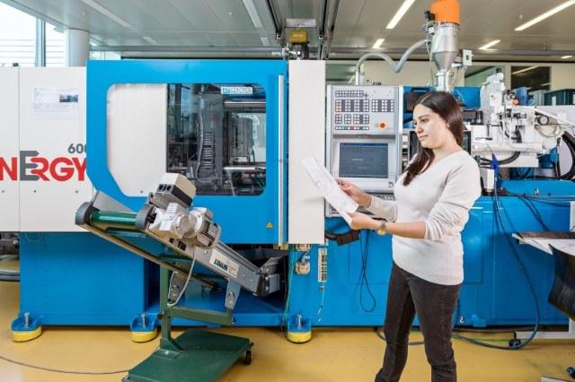 Eine Lernende neben einer Produktionslinie